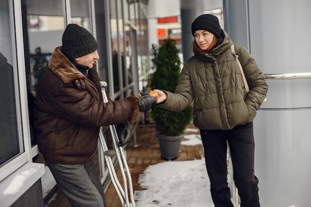 Dakloos in een winterstad. man die om voedsel vraagt.
