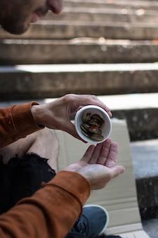 Dakloze man die zijn wisselgeld telt