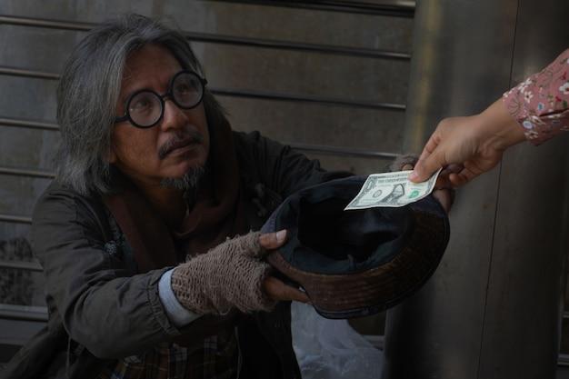 Dakloze man gaat zitten op de loopbrug in de stad