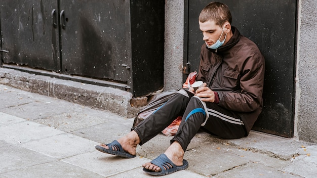 Dakloze man met medisch masker en beker