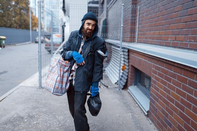 Dakloze man met tas op straat in de stad.