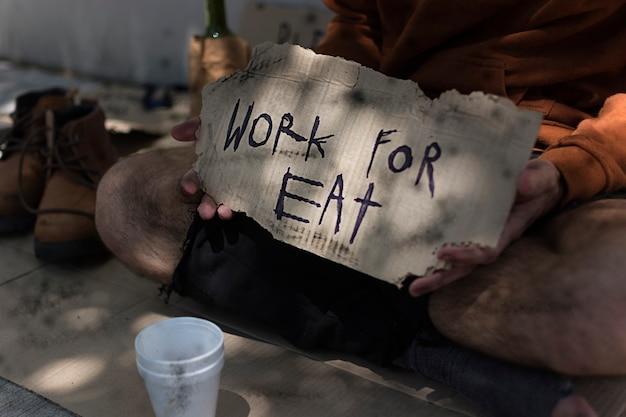Dakloze man met werk voor eten teken