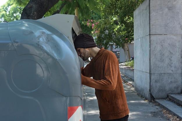 Daklozen kijken door vuilnisbakken op straat