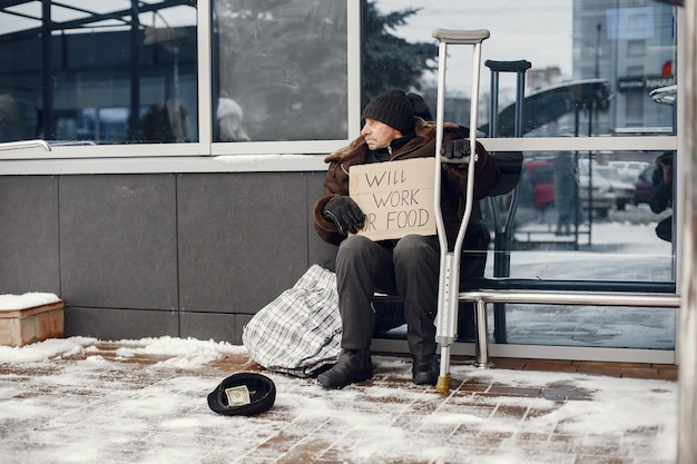 Daklozen zitten in de buurt van gebouw.