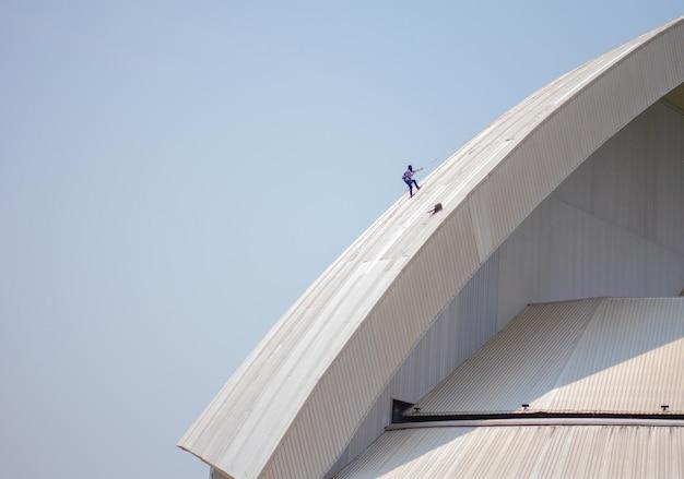 Dakreparateur die een beschadigd dak inspecteert
