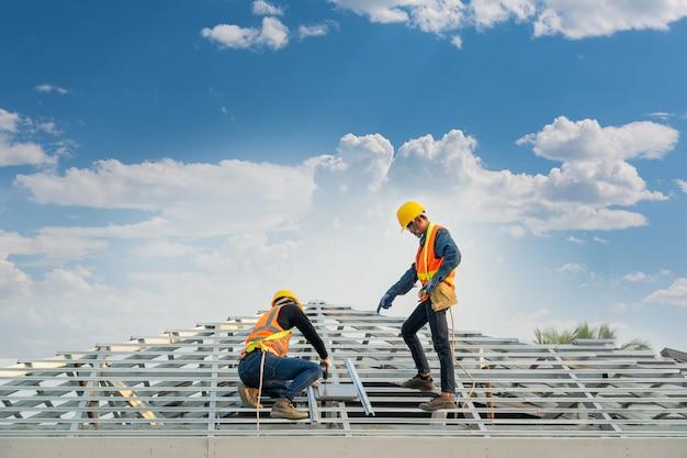 Dakwerker in speciale beschermende werkkleding en handschoenen, met behulp van een pneumatisch pistool en het installeren van betonnen dakpan op het nieuwe dak, concept van woningbouw in aanbouw.