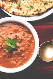 Dal makhani of daal makhni is een populair gerecht uit punjab, india gemaakt met hele zwarte linzen, rode kidneybonen, boter en room en geserveerd met knoflook naan of indiaas brood of roti