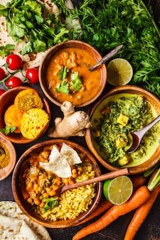 Dal, palak paneer, curry, rijst, chapati, chutney in houten kommen op donkere tafel.