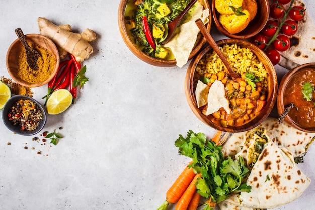 Dal, palak paneer, curry, rijst, chapati, chutney in houten kommen op witte tafel.