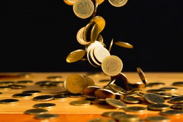 Dalend gouden muntstukkengeld op houten lijst