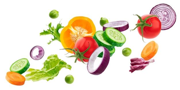Dalende mix van verschillende groenten, verse ingrediënten voor de salade geïsoleerd op een witte ondergrond