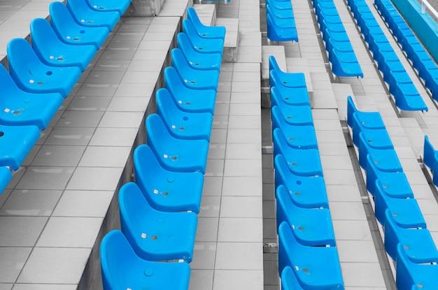 Dalende rijen heldere toeschouwersstoelen in een sportfaciliteit.