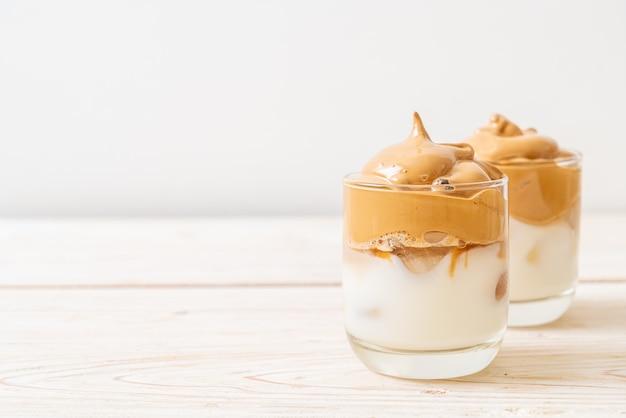 Dalgona koffie. iced fluffy creamy whipped trend drink met koffieschuim en melk.