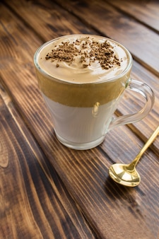 Dalgona-koffie in de glaskop op de bruine houten achtergrond. locatie verticaal.