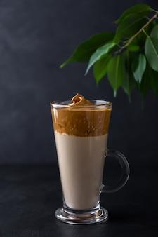 Dalgona koffie in een glazen beker op een zwarte ruimte