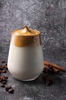 Dalgona-koffie in glas naast pijpjes kaneel en anijsplant