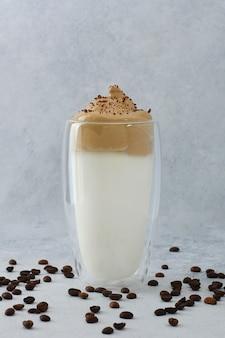 Dalgona koffie in hoog glas versierd met koffiebonen en chocolade. schuimend latte met koffieschuim op lichte achtergrond.