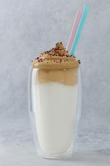 Dalgona koffie met kleurrijke hagelslag, chocolade en rietjes in hoog dubbelwandig glas. frothy coffee is een drankje met opgeklopte instant koffie, suiker en melk.