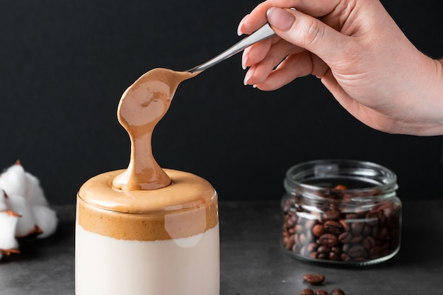 Dalgona-koffie trendy drankje op zwarte achtergrond vrouw zet pluizig zoet schuim in glas met melk