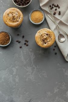 Dalgona slagroomkoffie, instant, room, ijskoffie. cocktail met koffie, melk en ijsblokjes op grijs