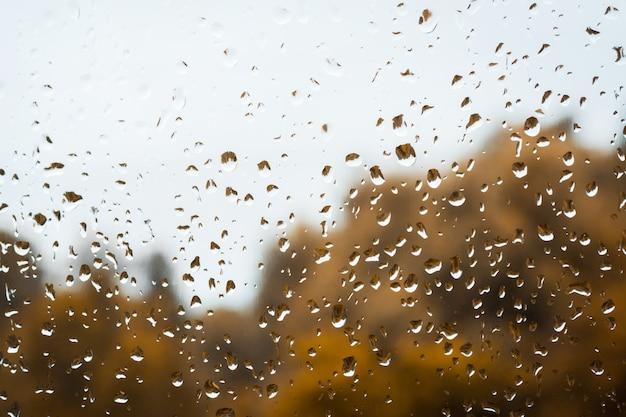 Dalingen van regen op venster tegen sombere regenachtige hemel en gouden bomenachtergrond