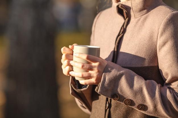 Dalingsconcept - de herfstvrouw het drinken koffie op parkbank onder dalingsgebladerte