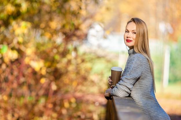 Dalingsconcept - mooie vrouw het drinken koffie in de herfstpark onder dalingsgebladerte