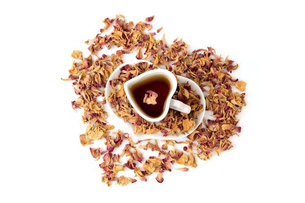 Damast roos, gedroogde bloemblaadjes en thee geïsoleerd op wit. bovenaanzicht, plat leggen.