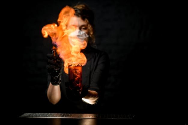 Dame aan de bar hagelslag op glas met alcoholische drank en vuur maken