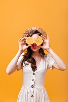 Dame bedekt haar ogen met sinaasappels. vrouw in strohoed en witte outfit blaast kus.