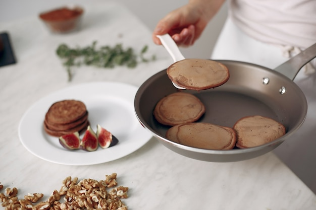 Dame bereidt dessert voor. banketbakker bakt pannenkoeken. vrouw heeft een koekenpan in zijn handen.
