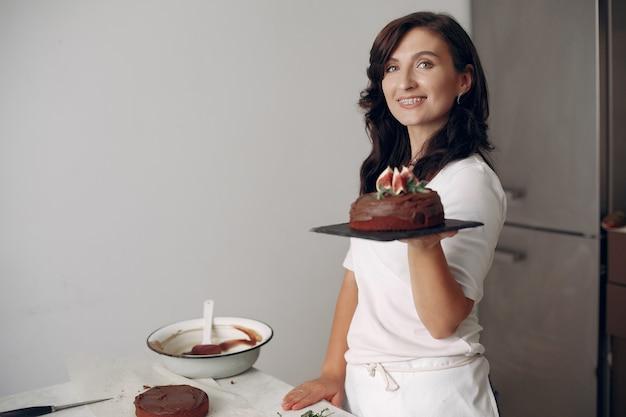 Dame bereidt dessert. vrouw bakt een cake. banketbakker met chocoladetaart.