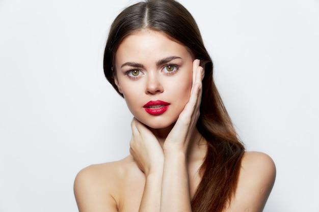 Dame blote schouders schone huid rode lippen handen in de buurt van gezicht aantrekkelijke look geïsoleerde achtergrond