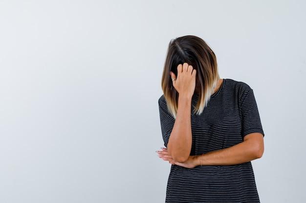 Dame buigt hoofd naar beneden in zwart t-shirt en kijkt depressief, vooraanzicht.