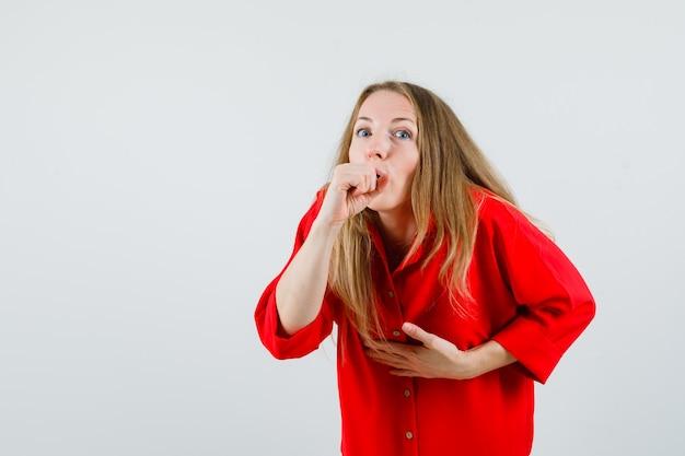 Dame die aan hoest in rood overhemd lijdt en ziek kijkt.