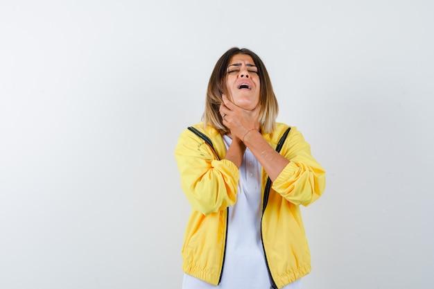 Dame die aan keelpijn in t-shirt, jas lijdt en ziek, vooraanzicht kijkt.