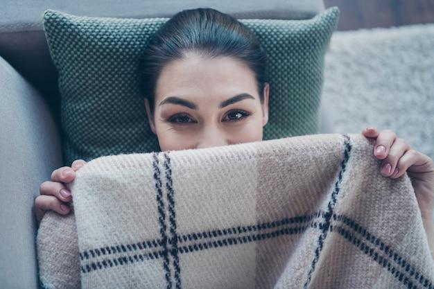 Dame die comfortabel op de bank ligt en het gezicht bedekt met een deken