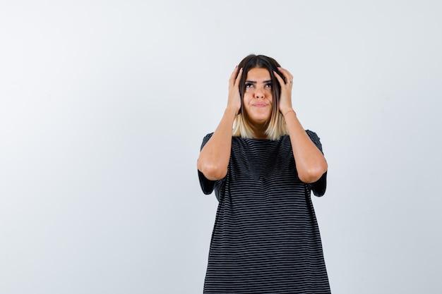 Dame die de handen op het hoofd in zwart t-shirt houdt en verward kijkt. vooraanzicht.