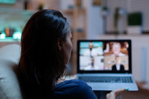 Dame die deelneemt aan webinar zittend op de bank. externe werknemer met online vergadering, videoconferentie overleg met collega's op videogesprek en webcamchat die voor laptop werkt