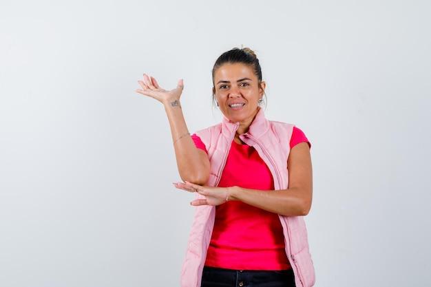 Dame die een welkomstgebaar toont in t-shirt, vest en er vrolijk uitziet