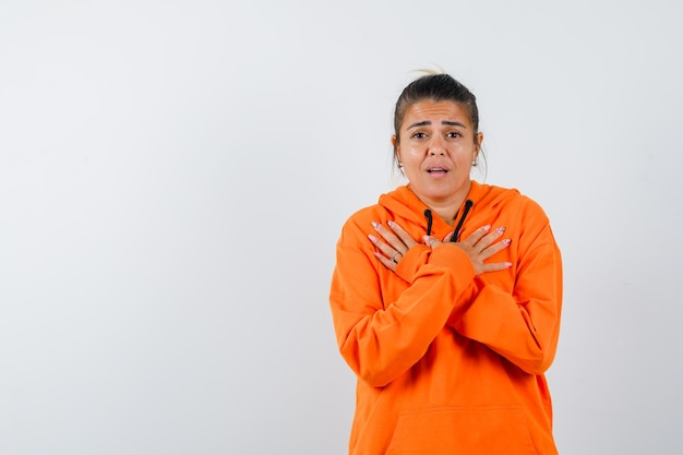 Dame die gekruiste handen op de borst houdt in oranje hoodie en er delicaat uitziet