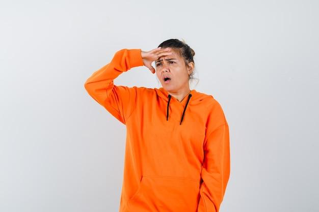 Dame die haar hand boven het hoofd houdt in een oranje hoodie en er verbaasd uitziet