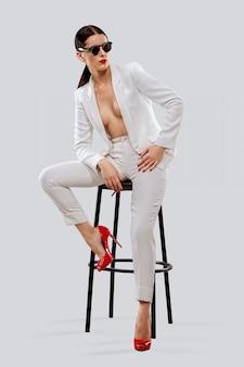 Dame die in wit broekpak en zonnebril op stoel zit