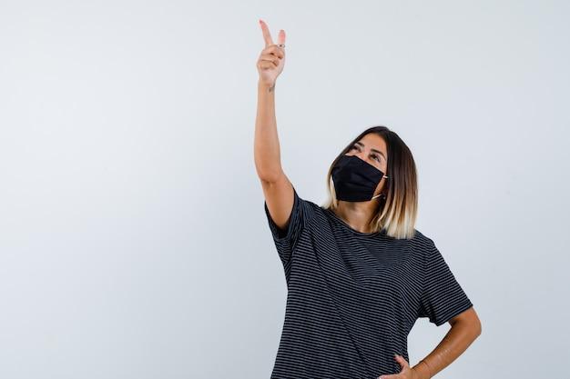 Dame die in zwarte kleding, medisch masker benadrukt en hoopvol, vooraanzicht kijkt.