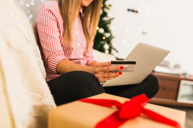 Dame die laptop met behulp van en creditcard houdt dichtbij giftdoos