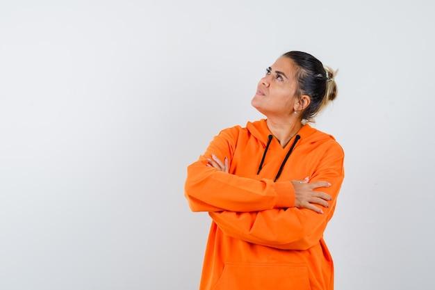 Dame die met gekruiste armen in oranje hoodie staat en er hoopvol uitziet