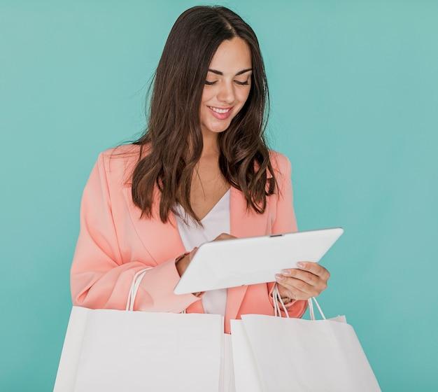 Dame die met winkelnetten tablet bekijkt