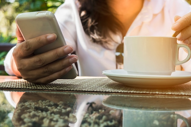 Dame die mobiele witte het drinken koffie gebruikt