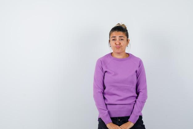 Dame die naar camera kijkt, lippen buigt, fronsend gezicht in wollen blouse en peinzend kijkt