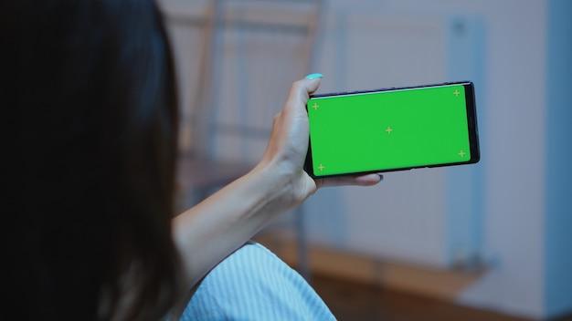 Dame die naar een smartphone met een groen scherm kijkt terwijl ze thuis op de bank zit te ontspannen. vrouw met een mobiele telefoon met mockup-sjabloon chromakey geïsoleerde mobiele telefoonweergave met behulp van techology internet